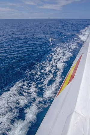 White boat side with Spanish flag and foamy blue Mediterranean sea with sky in Mallorca, Spain vertical image. 写真素材