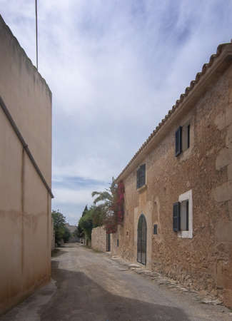 Old authentic empty gravel street with traditional stone buildings in Mallorca, Spain 写真素材 - 127062776