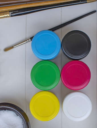 From above art materials for kids art class on white rustic wooden tray