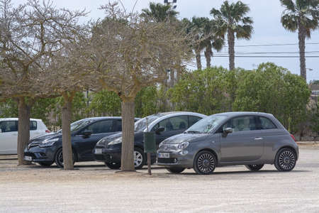 SES SALINES, MALLORCA, SPAIN - APRIL 15, 2019: Cars parked in row under trees outside Botanicactus park on an overcast day in the beginning of tourist season.