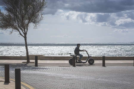 CAN PASTILLA, MALLORCA, SPAIN - APRIL 6, 2019: Scooter driver in backlight by the ocean on a windy and sunny day on April 6, 2019 in Can Pastilla, Mallorca, Spain. 報道画像