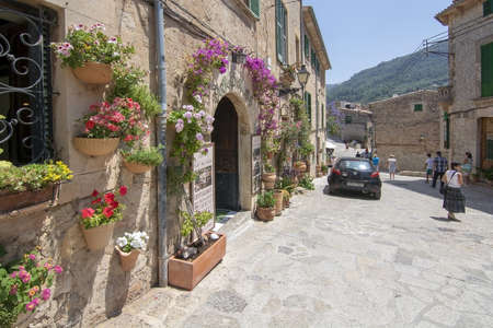 VALLDEMOSSA, MALLORCA, SPAIN - JUNE 20, 2019: Flower decorated facade in picturesque village on a sunny day on June 20, 2019 in Valldemossa, Spain.