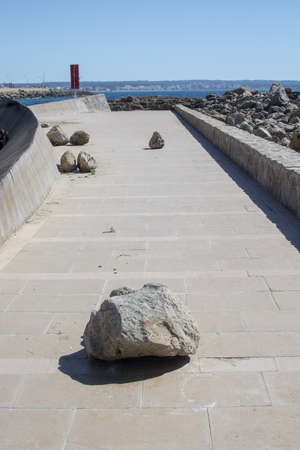 Large rocks thrown up on walkway seaside after winter storm in Can Pastilla, Mallorca, Spain. 写真素材