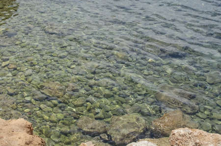 Shallow transparent green ocean water with rocks om Mallorca, Spain for background texture. 写真素材