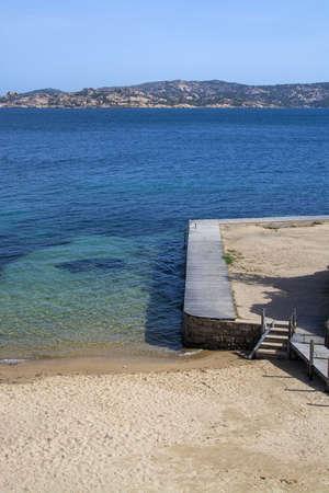 Sandy beach and wooden boardwalk near green water in Costa Smeralda, Sardinia, Italy. 写真素材