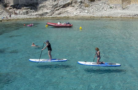 MALLORCA, SPAIN - JUNE 23, 2019: Stand up paddlers on clear turquoise water near the shore on a sunny day on June 23, 2019 in Mallorca, Spain. 報道画像