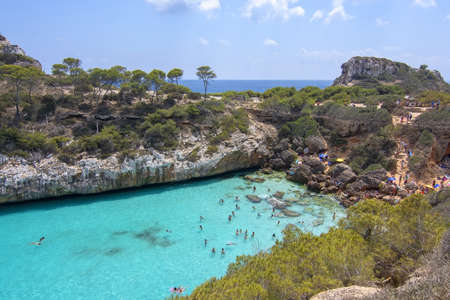 CALO DES MORO, MALLORCA, SPAIN - JULY 27, 2019: Small extremely turquoise bay and steep cliffs on a sunny day on July 27, 2019 in Calo des Moro, Mallorca, Spain.