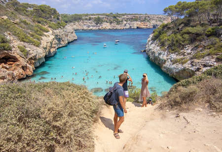 CALO DES MORO, MALLORCA, SPAIN - JULY 27, 2019: People hesitant to walk down to small extremely turquoise bay and steep cliffs on a sunny day on July 27, 2019 in Calo des Moro, Mallorca, Spain.