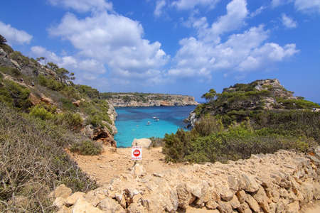 CALO DES MORO, MALLORCA, SPAIN - JULY 27, 2019: Danger sign by small extremely turquoise bay and steep cliffs on a sunny day on July 27, 2019 in Calo des Moro, Mallorca, Spain. 報道画像
