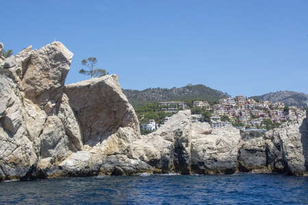 Coastal rocks and village in the distance in southwest Mallorca, Spain.