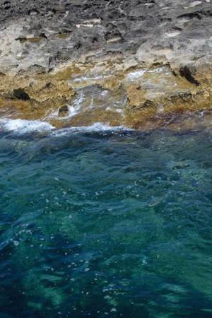 Natural coastline detail with green clear sea water and limestone rocks on a sunny summer day in Mallorca, Spain.