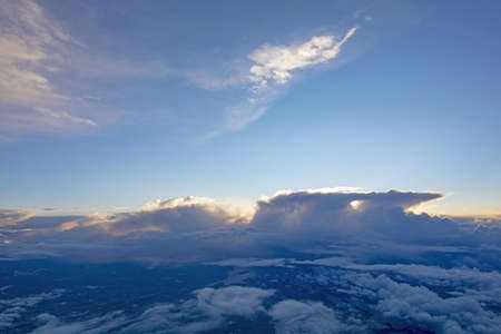 Dreamy aerial cloud landscape flying high above the Earth with thunderclouds on a sunny day. 写真素材