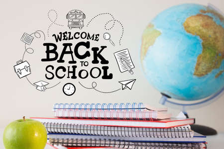 Composite of welcome back to school text with notebooks globe and apple