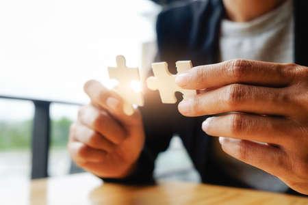 Geschäftsfrau Hände, die Puzzle verbinden. Geschäftslösungen, Erfolg und Strategiekonzept. Geschäftsmannhand, die Puzzle verbindet. Schließen Sie Foto mit selektivem Fokus.