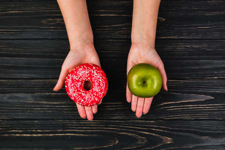 Donut and apple in hands