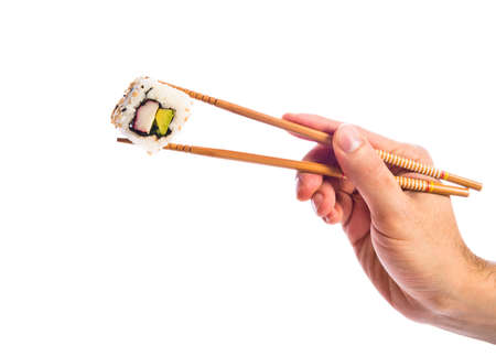 hand holding sushi with chopsticks Stock Photo