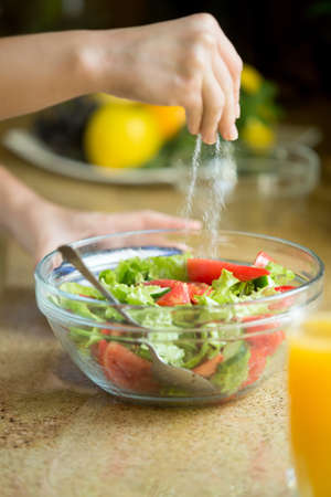 Hands salting a green salad, spoon in the bowl. Concept photo Stock Photo