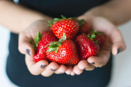 Lady holding fresh ripe strawberries in her hands