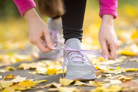 Hands tying trainers shoelaces on the autumn pave, full of yellow leaves. Concept photo, horizontal, closeup Stock Photo