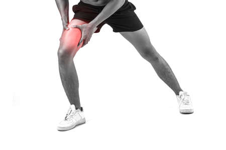 Young sport man with strong athletic legs holding knee with his hands in pain after suffering ligament injury  isolated on white. Stock Photo
