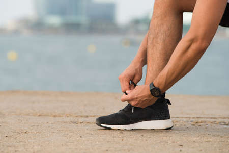 Close-up of man tying shoelaces outdoors. Unrecognizable sportsman with hairy legs putting foot on ground while tying running shoe. Jogging like hobby concept