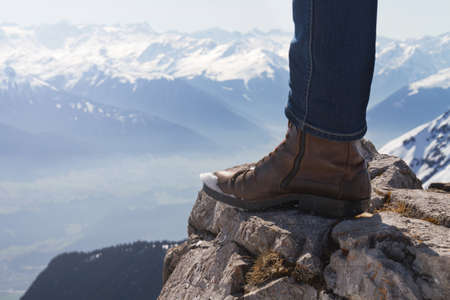 Male feet on edge of mountain. Mountain background