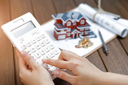 A female hand operating a calculator in front of a Villa house model Stock Photo - 107755961