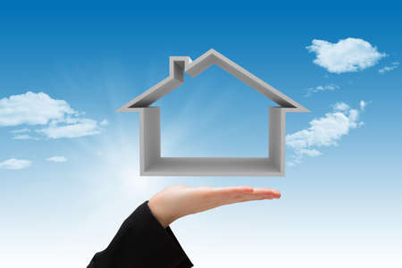 Composite image of hand carrying house with sky background Stock Photo - 107755964