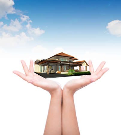 House in human hand over blue sky