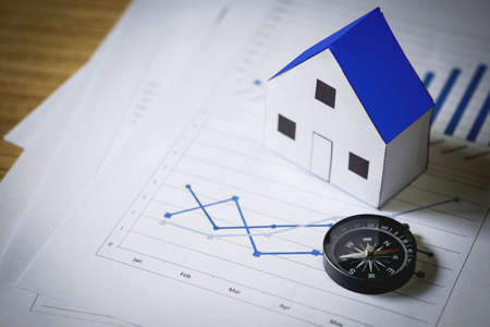 House model and compass on plan background, Real estate concept. Stock Photo - 107779620