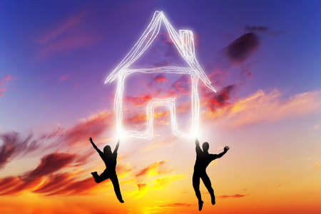 Happy couple jump and make a house symbol of light. Dreaming about new home, mortgage, new life together. Sunset sky Stock Photo
