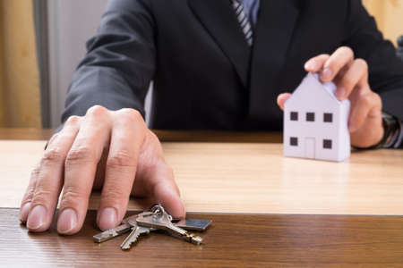 Real estate agent with house model and keys. Standard-Bild