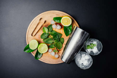 Mojito cocktail making. Mint, lime, lemon, ice ingredients and bar utensils. Top view. Copy space. Stock Photo