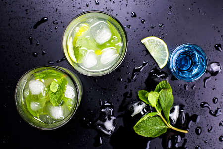 Tasty fragrant refreshing mojito with lime and mint on wet black table in bar or restaurant. Blue liqueur and cocktail mojito. Stock Photo