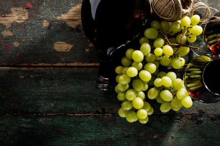 Tasty Fresh Green Grape with Wine Bottle and Wine Glass Red Wine on Old Green Vintage Background Top View Horizontal Copy Space Stock Photo - 107744879