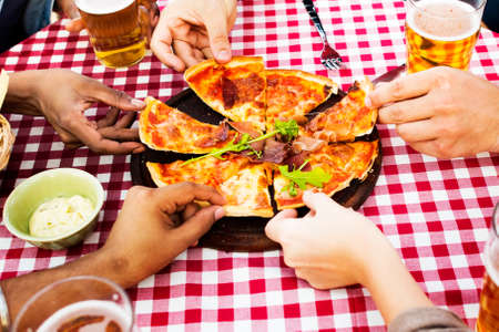 Group of diverse friends are gathering together eating pizza