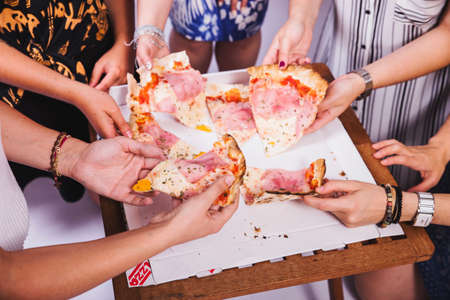 Group of various friends are gathering together eating pizza Standard-Bild