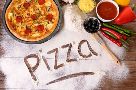 The word Pizza written in flour, with freshly baked pepperoni Pizza surrounded by various ingredients.