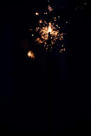 Closeup shot of a beautiful sparkler glowing on a dar bluish background