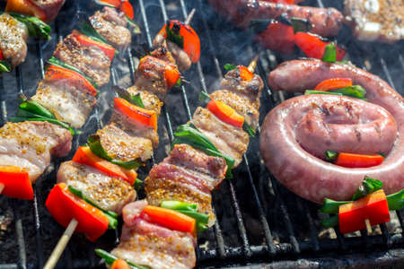 Close-up van heerlijke kip op houten scheef met verse groenten, knoflook, paprika gebakken op mangal barbecuegrill en rook