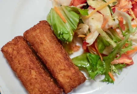 Potato croquette filled with cheese and herbs served with fresh green salad, tomatoes and pepper