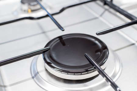 Close up shot of rapid burner on stainless steel gas hob with thin bar pan supports 版權商用圖片