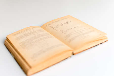Close up shot of an open old science book containing equations and graphs from different fields: math, physics, chemistry. The pages have the marks of the past as they got orange.
