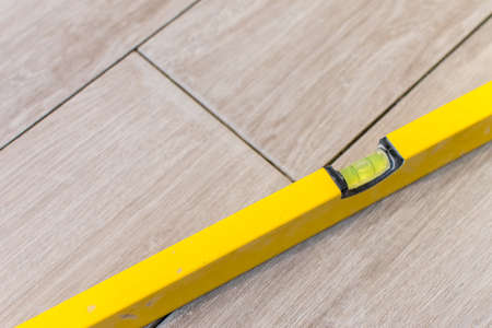Close up shot of a metal yellow spirit level placed on a newly installed yet not finished kitchen tiles