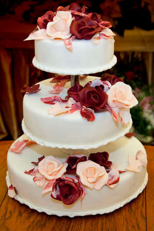 beautiful three-story wedding cake decorated with roses Stock Photo
