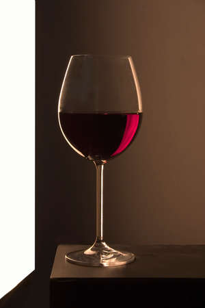 glass of red wine by the window