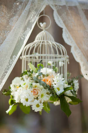 White flowers in cage, wedding decorations on sunny day