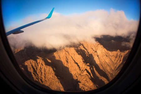 jetliner: An image taken from the window of a jetliner. There are clouds and mountains at sunrise