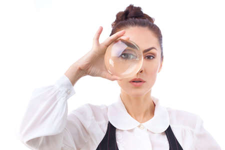 low scale magnification: Woman looking through a magnifying glass.This photo has been produced with these professionals : make-up artist, hair dresser and stylist. A professional retoucher gave it the final magic touch.