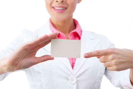 doctor holding gift: Business card closeup - businesswoman in white suit holding blank empty sign. Stock Photo
